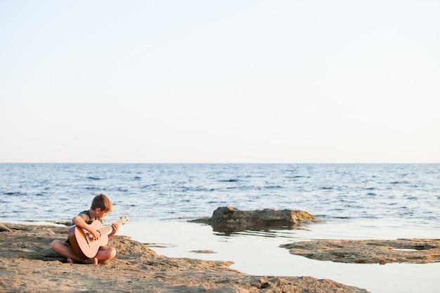 Junge, der gitarre durch den ozean spielt.