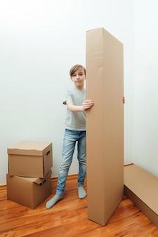 Junge, der großen karton hält glückliche familie mit kartons im neuen haus am umzugstag