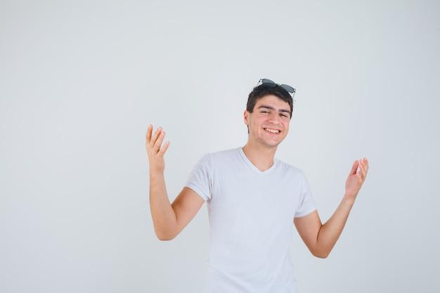Junge, der hände anhebt, während kamera in t-shirt betrachtet und fröhlich, vorderansicht schaut.