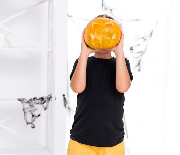 Junge, der halloween geschnitzten kürbis hält