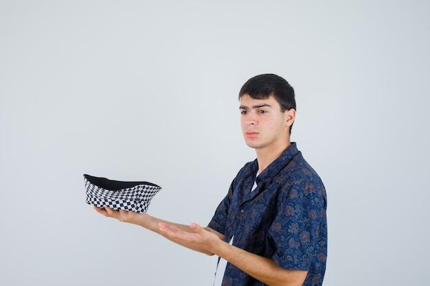 Junge, der hand als präsentationskappe im weißen t-shirt, im blumenhemd, in der kappe und im ernsthaften aussehen streckt. vorderansicht.