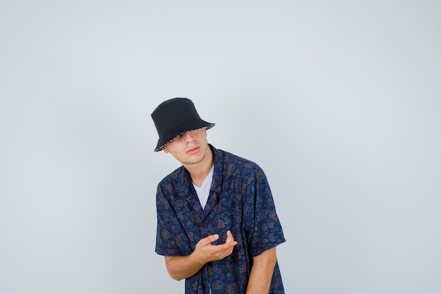 Junge, der hand streckt, wie etwas imaginäres in weißem t-shirt, blumenhemd, mütze hält und selbstbewusst, vorderansicht schaut.