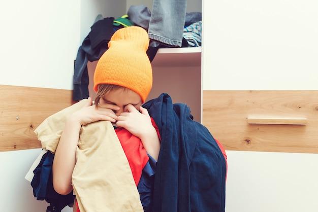 Junge, der haufen schmutziger kleidung hält unordentliches kinderzimmer zu hause. hausarbeit hausarbeit. chaos im kleiderschrank. müder betonter junge, der seine garderobe säubert