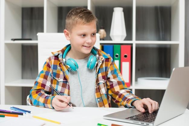 Junge, der hausarbeit mit laptop tut