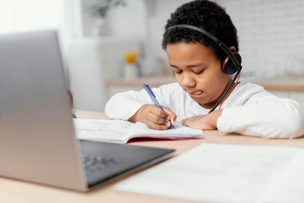 Junge, der hausaufgaben mit laptop macht