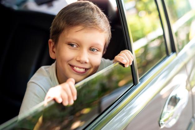 Junge, der heraus das autofenster schaut