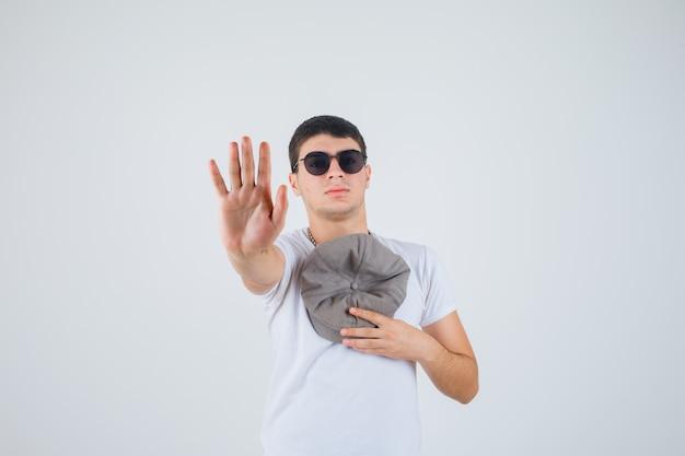 Junge, der hut auf brust hält, während handfläche im t-shirt zeigt und selbstbewusst aussieht. vorderansicht.