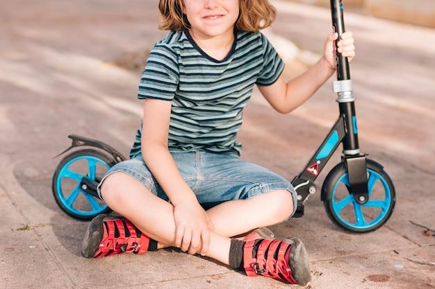 Junge, der im park mit roller sitzt