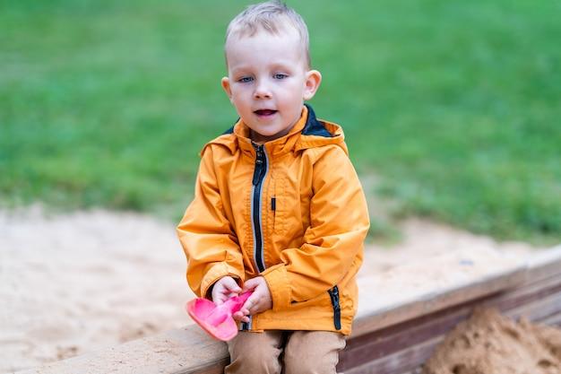 Junge, der im sandkasten sitzt