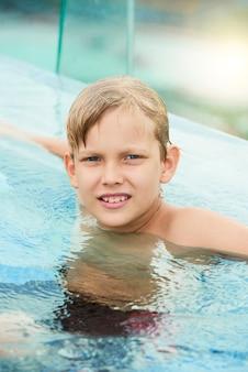 Junge, der im swimmingpool sich entspannt