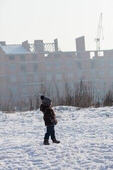Junge, der im winter spaziert und den kran auf einer baustelle beobachtet