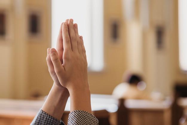 Junge, der in der kirchennahaufnahme mit kopienraum betet