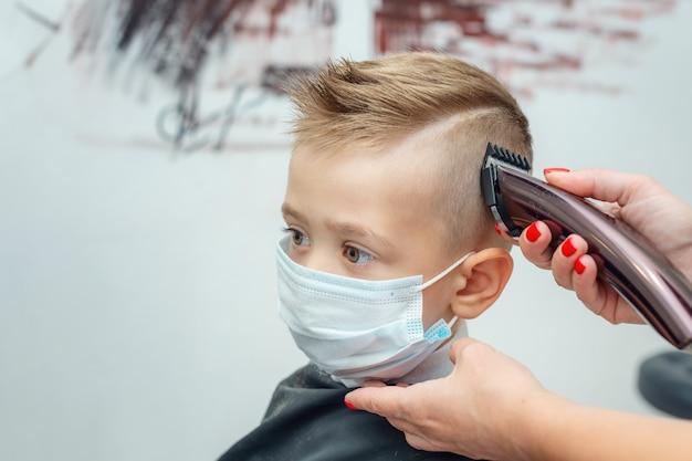 Junge, der in der schutzmaske am friseur sitzt, der einen haarschnitt schneidet. neue normalität