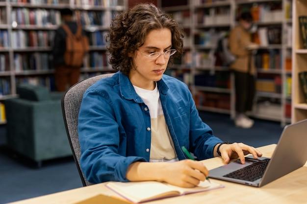 Junge, der in der universitätsbibliothek studiert