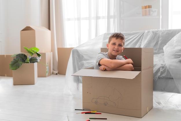 Junge, der in einer kiste spielt, bevor er mit seiner familie auszieht