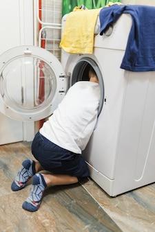 Junge, der innere waschmaschine schaut