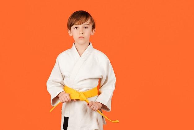 Junge, der karate auf farbigem hintergrund praktiziert, kopieren raum kindersportkonzept gesunde sportliche kindheit