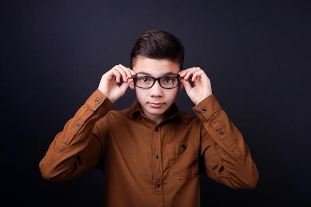 Junge, der kerl stellt seine brille auf einen schwarzen hintergrund ein