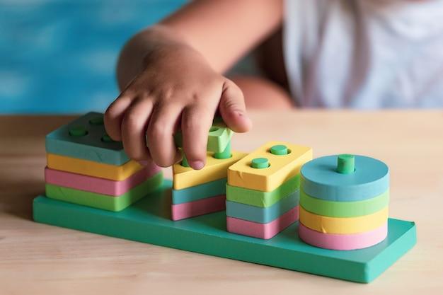 Junge, der kinderspielzeug für das lernen für fähigkeiten spielt