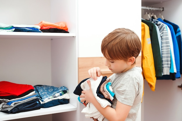 Junge, der kleidung im kleiderschrank organisiert, nahaufnahme. kind, das einen kleiderstapel auf das regal legt. bestellung im schrank. kleiderschrank mit kinderkleidung.