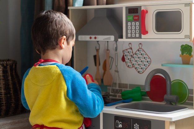Junge, der koch mit einer spielzeugküche zu hause spielt