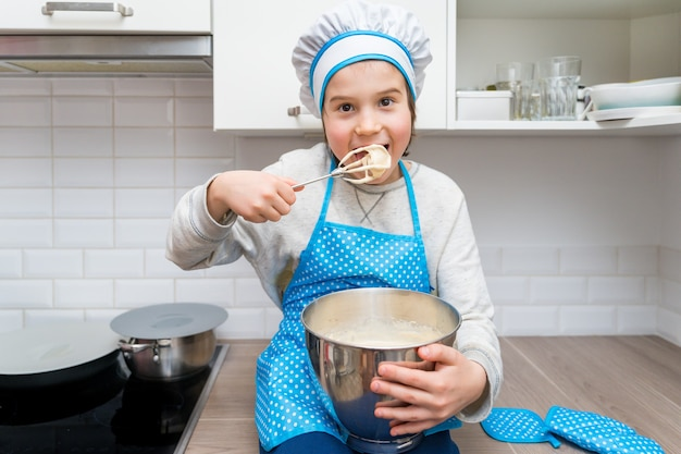 Junge, der kochmütze und schürze trägt, die in einer küche backen