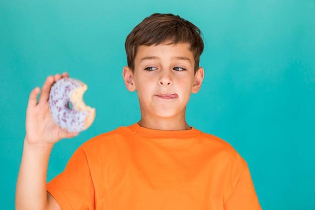 Junge, der köstlichen glasierten donut betrachtet