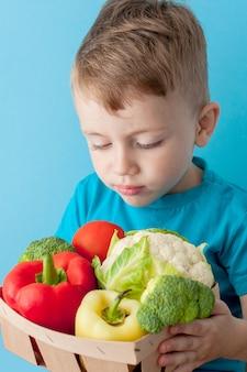 Junge, der korb mit frischgemüse auf blauem hintergrund hält. veganes und gesundes konzept.