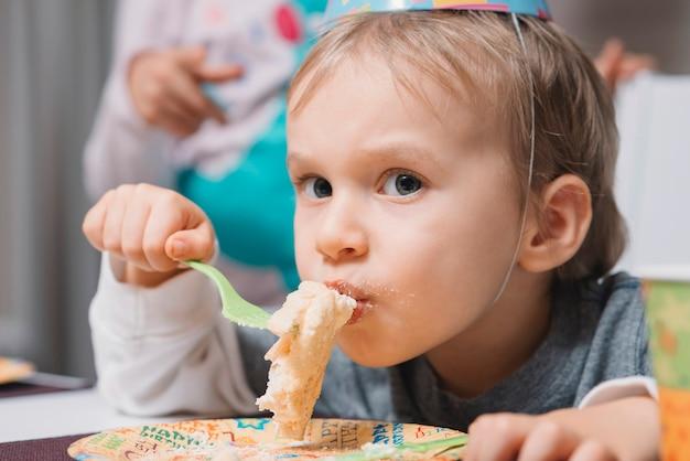 Junge, der kuchen auf geburtstagsfeier isst