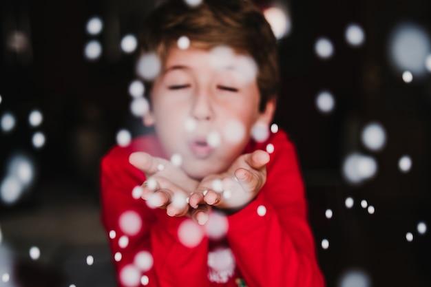 Junge, der künstliche schneeflocken zu hause bläst