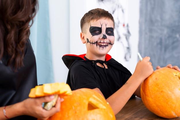 Junge, der kürbis für halloween schnitzt