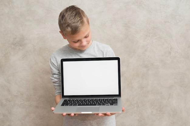 Junge, der laptopschablone darstellt