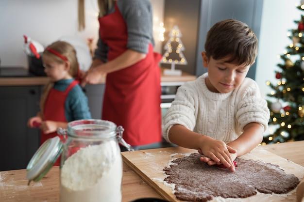 Junge, der lebkuchenplätzchen während weihnachten macht