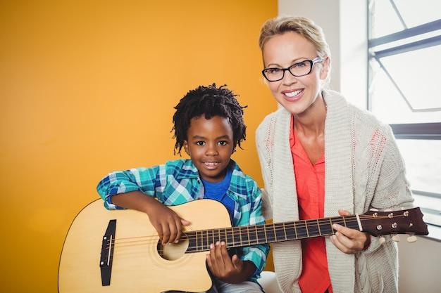 Junge, der lernt, wie man gitarre spielt