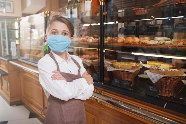 Junge, der medizinische gesichtsmaske und schürze trägt, die in seiner familienbäckerei arbeitet