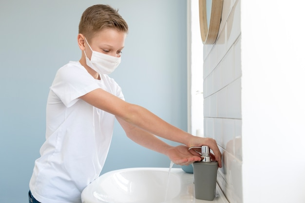 Junge, der medizinische maske trägt und seine hände wäscht