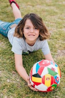 Junge, der mit ball auf gras spielt