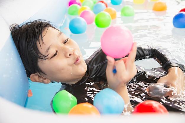 Junge, der mit buntem ball im kleinen swimmingpoolspielzeug spielt