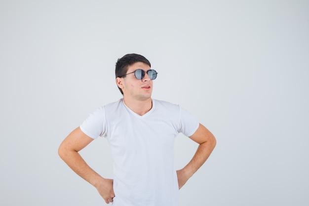 Junge, der mit den händen auf der taille im t-shirt aufwirft und selbstbewusst aussieht. vorderansicht.