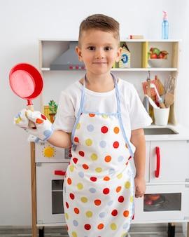 Junge, der mit einem kochspiel drinnen spielt