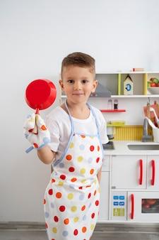 Junge, der mit einem kochspiel spielt