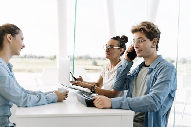 Junge, der mit einem mobiltelefon an einem arbeitstisch mit anderen leuten in einem coworking spricht