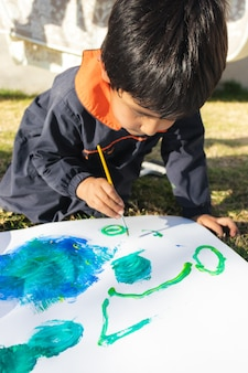Junge, der mit einem pinsel auf einer weißen oberfläche mit blauer farbe malt, einen kittel trägt, im hof an einem sonnigen tag mit kleidung im hintergrund
