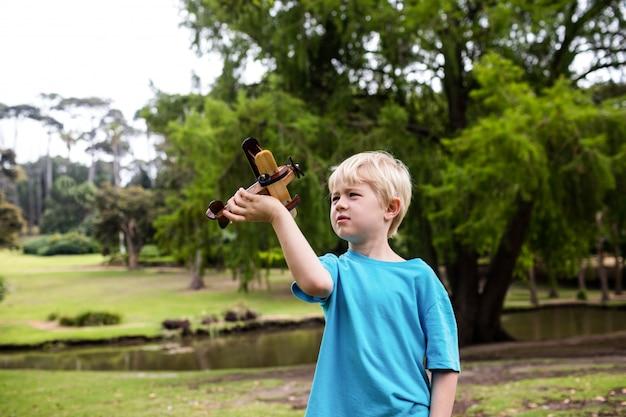 Junge, der mit einem spielzeugflugzeug spielt