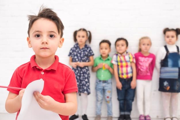 Junge, der mit einer kindergruppe zeichnet
