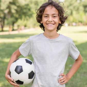 Junge, der mit fußball spielt