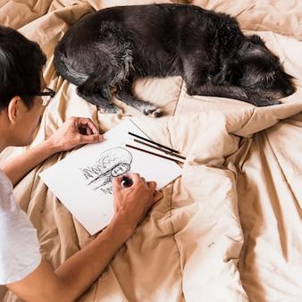 Junge, der mit holzkohle mit hund zeichnet