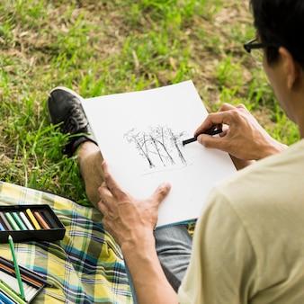 Junge, der mit holzkohle zeichnet
