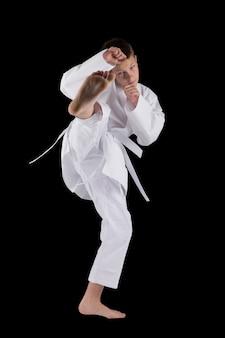 Junge, der mit karatetechniken im studio auf dem schwarzen lokalisiert aufwirft