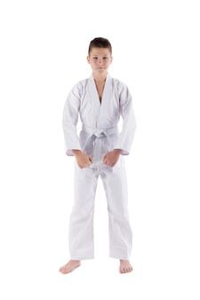 Junge, der mit karatetechniken im studio auf weiß lokalisiert aufwirft